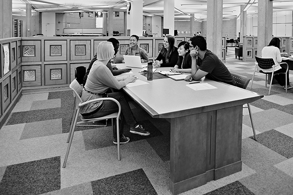 black and white photo of a group of students working at a table