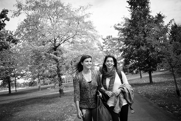 black and white photo of two students walking on a campus foot path