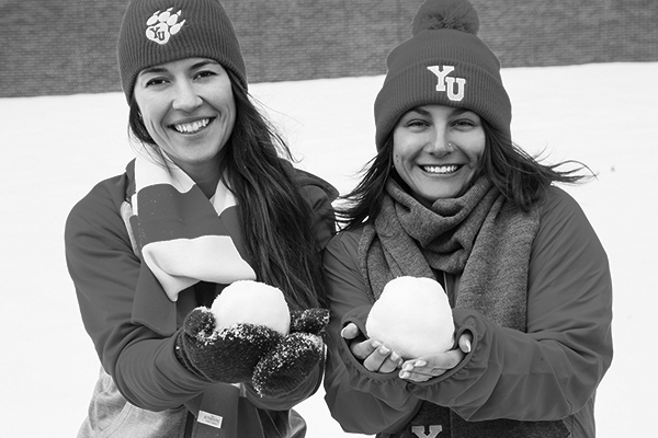black and white photo of two students holding snowballs